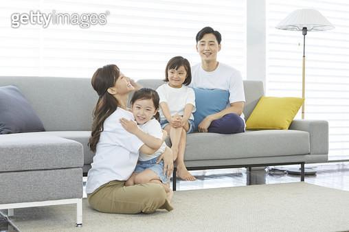엄마에게 안겨있는 어린딸과 아빠와 함께 소파에 앉아있는 큰딸 - gettyimageskorea