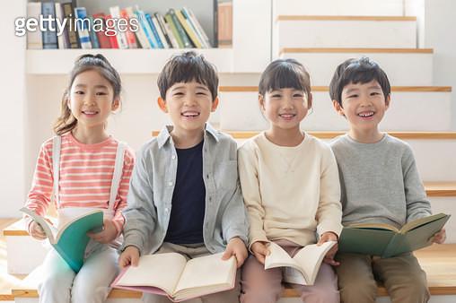 나란히 앉아 책을 보는 아이들 - gettyimageskorea