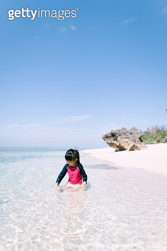 Little girl playing in shallow tropical water with white sand beach, Japan - gettyimageskorea
