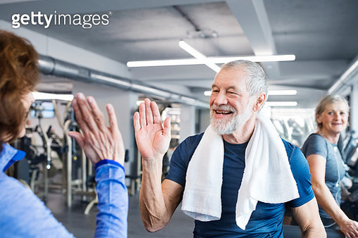 Happy senior man and woman high fiving after working out in gym - gettyimageskorea