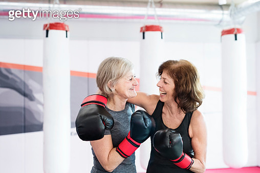 Two happy senior women with boxing gloves embracing in gym - gettyimageskorea