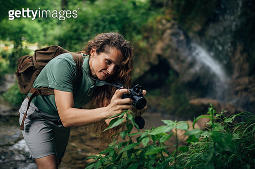 One woman, lady explorer and biologist standing in nature alone, taking pictures with camera. - gettyimageskorea