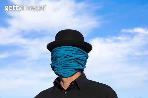 Man wearing bowler hat with rope wrapped around his face - gettyimageskorea