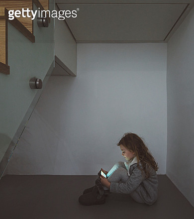 Young Girl using smartphone under stairs - gettyimageskorea