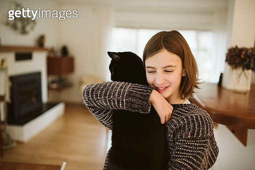 Affectionate girl holding black cat - gettyimageskorea