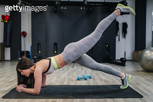 Young beautiful woman doing exercises and working hard in gym and enjoying her training process. - gettyimageskorea