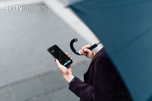 Businesswoman With Umbrella, Checking Stock Market On Smart Phone In The Rain - gettyimageskorea