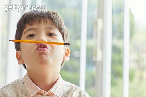 연필을 물고 있는 아이 - gettyimageskorea