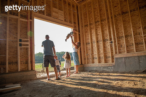 Young family standing in rural barn under construction - gettyimageskorea