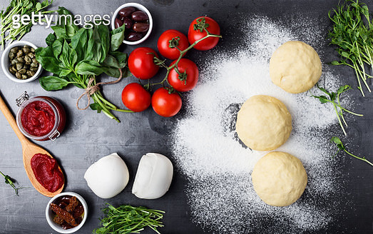 Gourmet pizza with sprouts topping preparation. Raw pizza dough with ingredients viewed from above - gettyimageskorea