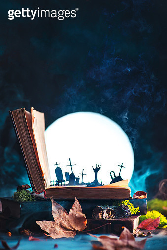 Open book with silhouettes of graveyard and zombie hands with full Moon. Halloween still life with magical book, creative and funny horror concept - gettyimageskorea