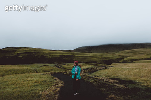 Woman walks in green valley with moss in Iceland - gettyimageskorea