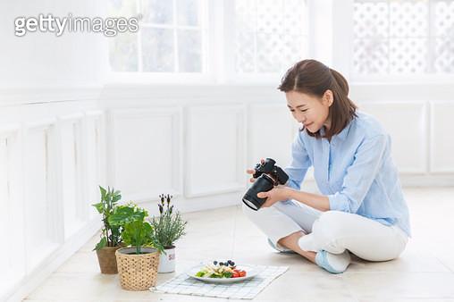 바닥에 앉아 카메라로 음식을 촬영하고 있는 여성 - gettyimageskorea