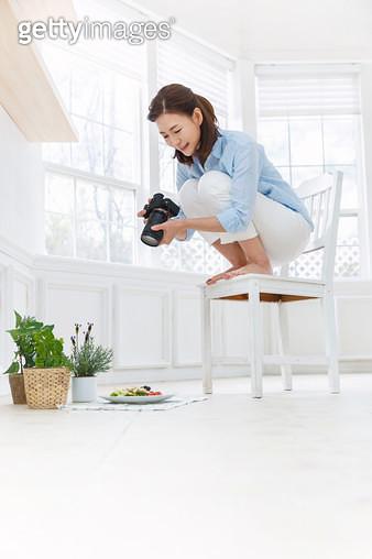 의자에 앉아 카메라로 음식을 촬영하고 있는 여성 - gettyimageskorea