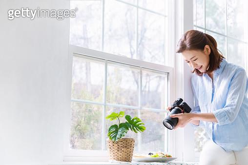 창틀에서 카메라로 음식을 촬영하고 있는 여성 - gettyimageskorea