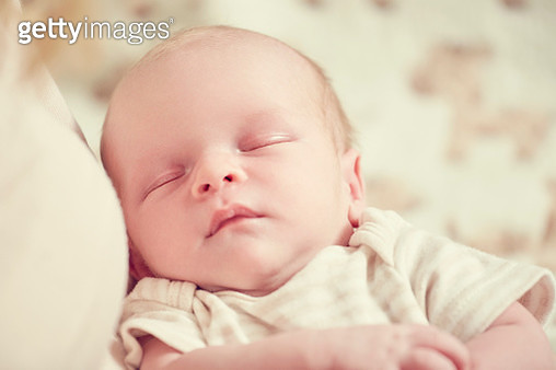 Newborn baby boy, sleeping in mothers arms, close-up - gettyimageskorea