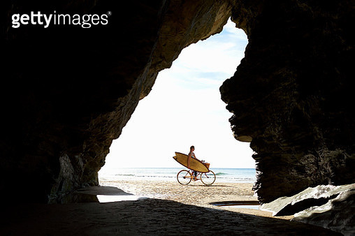 A woman cycles along a Cornish beach with her surfboard. - gettyimageskorea