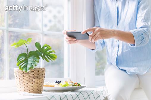 창틀에서 핸드폰으로 음식을 찍고 있는 여성 - gettyimageskorea