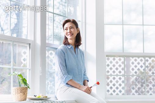 과일을 들고 창밖을 바라보는 여성 - gettyimageskorea