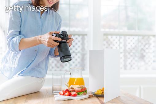 테이블 위에 앉아 카메라로 과일과 샌드위치를 촬영하는 여성 - gettyimageskorea