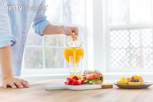 컵에 오렌지 주스를 따르는 손 - gettyimageskorea