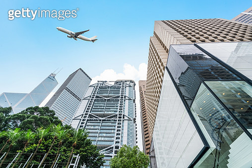 low angle view of airplane flying over financial district - gettyimageskorea