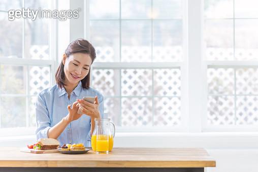 식탁에 앉아 핸드폰을 보고 있는 여성 - gettyimageskorea