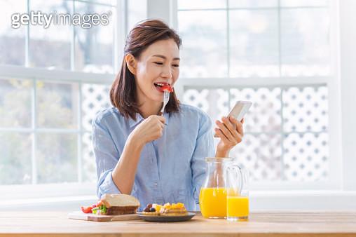 과일을 먹으며 핸드폰을 보는 여성 - gettyimageskorea