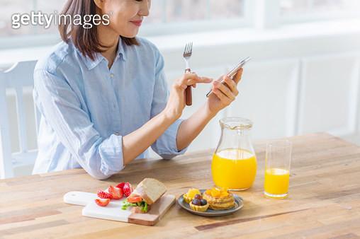 포크를 들고 핸드폰을 보는 여성 - gettyimageskorea