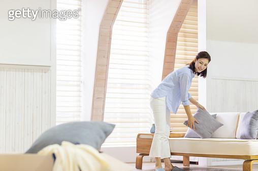 쇼파에 있는 베개를 정리하고 있는 여성 - gettyimageskorea