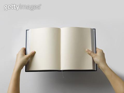 펼친 책을 붙잡고 있는 손 - gettyimageskorea