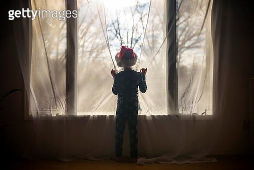 Boy wearing a Santa Hat looking through a window - gettyimageskorea