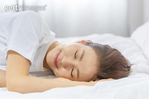 침대에 누워 잠을 자고 있는 여성 - gettyimageskorea