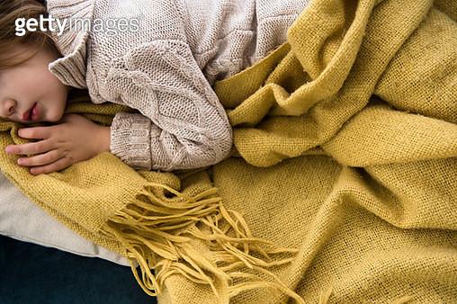 Girl (4-5) lying on sofa covered with blanket - gettyimageskorea