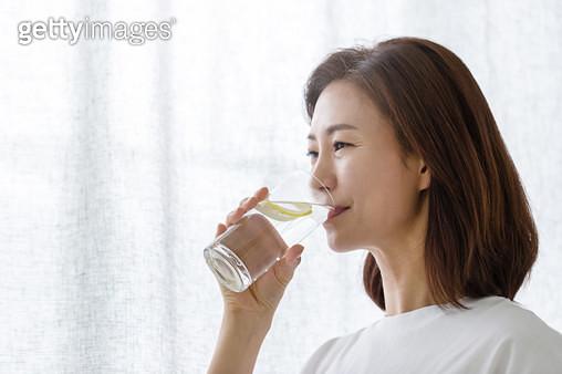 창문 옆에서 물을 마시고 있는 여성 - gettyimageskorea