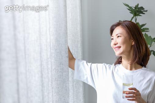 물잔을 들고 커튼을 열며 창밖을 바라보는 여성 - gettyimageskorea