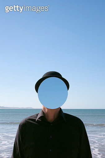 Morocco, Essaouira, man wearing a bowler hat with mirror in front of his face at the sea - gettyimageskorea