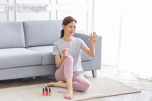 쇼파에 앉아 매니큐어를 바르고 있는 여성 - gettyimageskorea