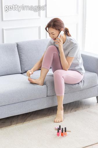 전화통화를 하며 메니큐어를 바르고 있는 여성 - gettyimageskorea