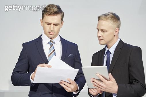태블릿피씨와 서류를 보는 두명의 비즈니스맨 - gettyimageskorea
