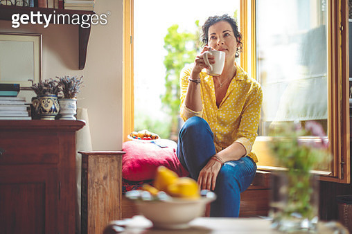 Mature woman is having the morning coffee at home - gettyimageskorea