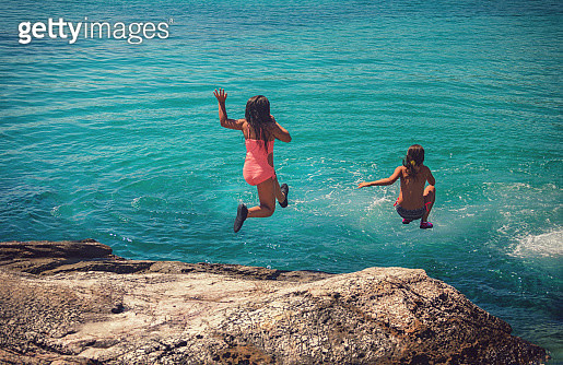 Little girls having fun on summer vacation, they diving from rock into crystal blue sea - gettyimageskorea