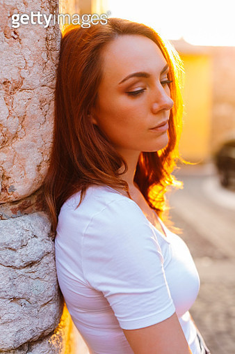 Portrait of redheaded woman leaning against wall at sunset - gettyimageskorea