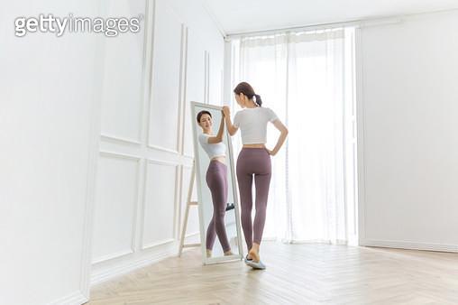 거울을 보면서 바디체크를 하는 여성 - gettyimageskorea