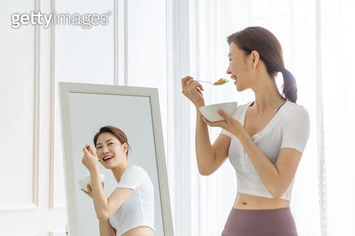 시리얼을 들고 거울을 바라보는 여성 - gettyimageskorea
