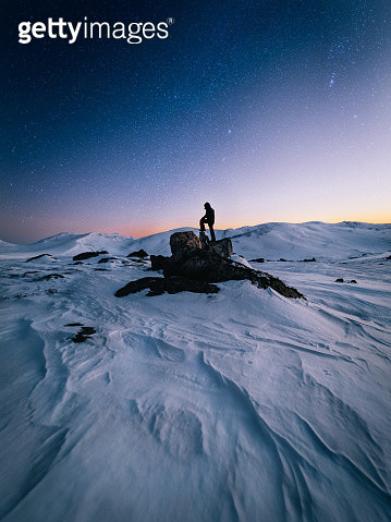 Silhouette Man Standing On Rock At Snow Covered Mountains Against Sky - gettyimageskorea