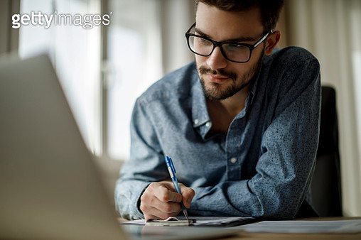 Young man working on laptop and taking notes - gettyimageskorea