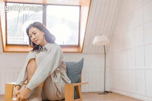 의자에 앉아 우울해 하는 표정의 여성 - gettyimageskorea