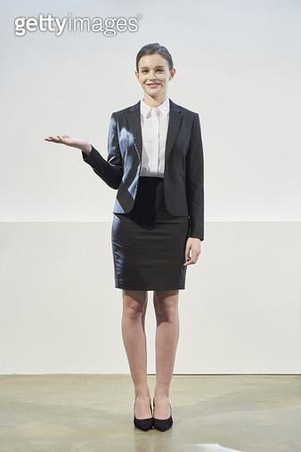 한 손을 들고 서있는 정장 차림의 비즈니스우먼 - gettyimageskorea