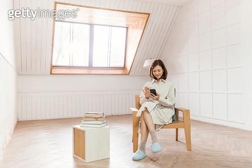의자에 앉아 핸드폰을 하며 즐거워 하는 여성 - gettyimageskorea